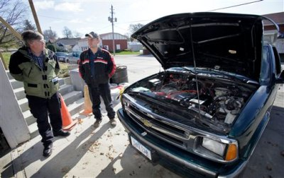 Mike Howard (left) stands next to Elk Horn's only electric vehicle, a Chevrolet S10 that he converted for a customer